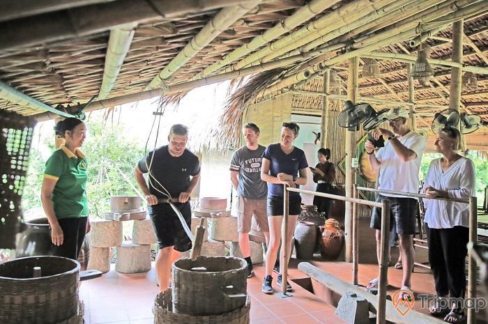 Du khách tham gia xay lúa, giã gạo tại khu nhà