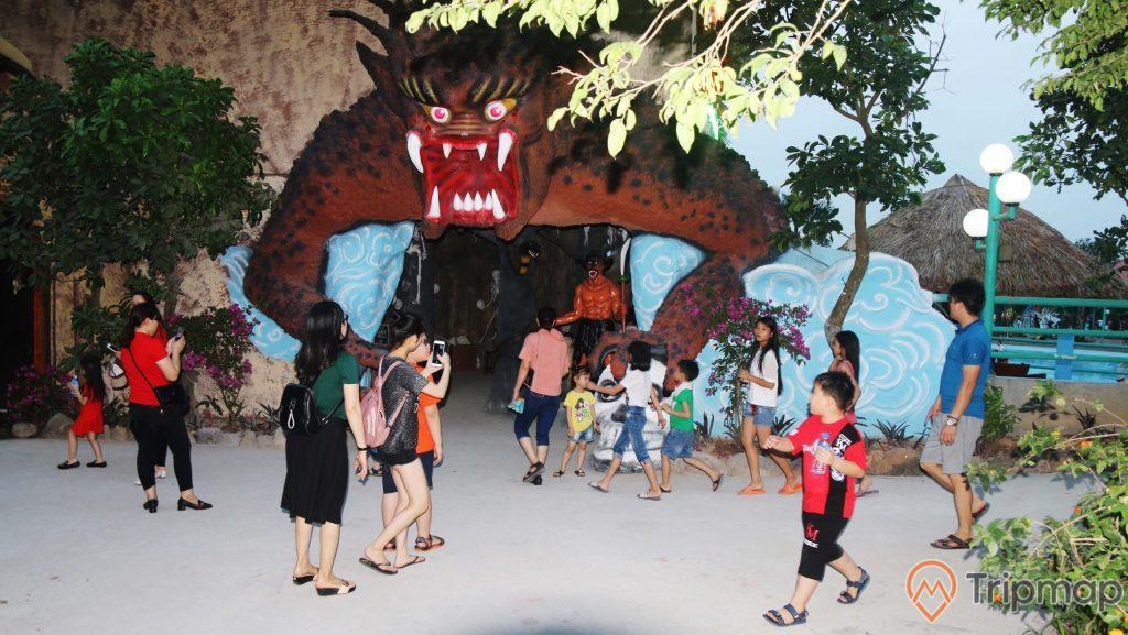 Khu trải nghiệm 18 tầng địa ngục, nhiều trẻ em đang đứng trên nền đường màu xám, mô hình quỷ đang nhe răng, nhiều cây xanh