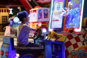 Khu video game xu xèng, cậu bé đang đội mũ xanh chơi trò chơi, máy điện tử xu xèng