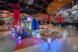 Khu video game xu xèng, nhiều máy chơi game, nhiều bộ bàn ghế ở phía xa, nền gạch nhiều màu sắc