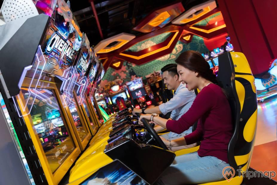 2 người, một đàn ông và một phụ nữ đang chơi video game tại khu video game xu xèng khu đồi huyền bí, ảnh chụp trong nhà