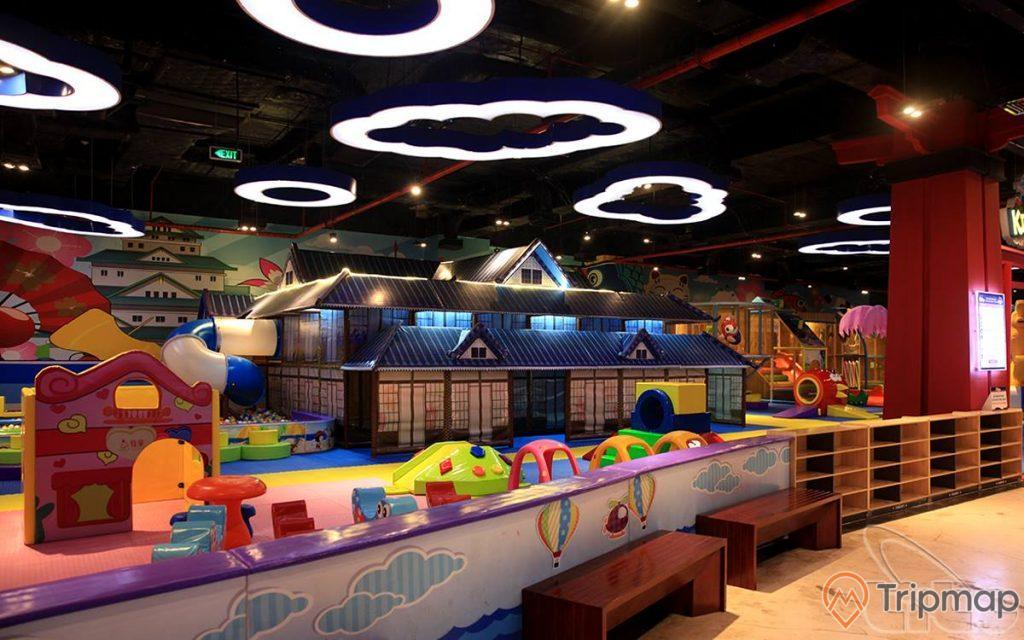Khu vui chơi trẻ em KIDOLAND, mô hình nhà màu xanh, ghế màu nâu, nền nhà bằng gạch màu vàng nhạt, trần nhà màu nâu, nhiều mô hình đám mây phát sáng