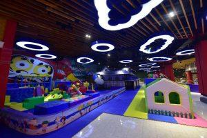 Khu vui chơi trẻ em KIDOLAND, nền gạch bằng đá màu vàng nhạt, trần nhà bằng gỗ, nhiều mô hình nhà vui chơi cho trẻ em, nhiều mô hình đám mây phát sáng