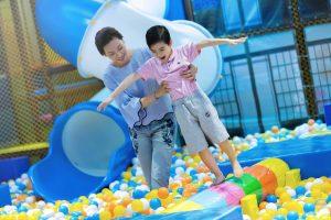 Khu vui chơi trẻ em KIDOLAND, nhà bóng, người phụ nữ đang đưa tay đỡ cậu bé, bóng nhựa nhiều màu sắc
