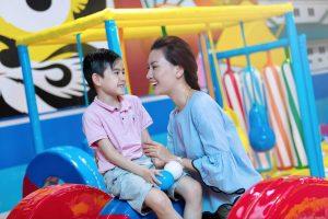Khu vui chơi trẻ em KIDOLAND, người phụ nữ mặc áo xanh đang cầm tay cậu bé mặc áo hồng
