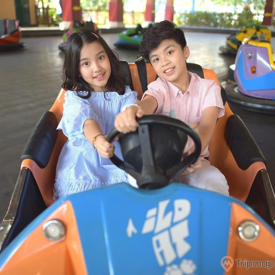Trò chơi thú vị trong Khu vui chơi trẻ em KIDOLAND, bé trai và bé gái ngồi trên xe