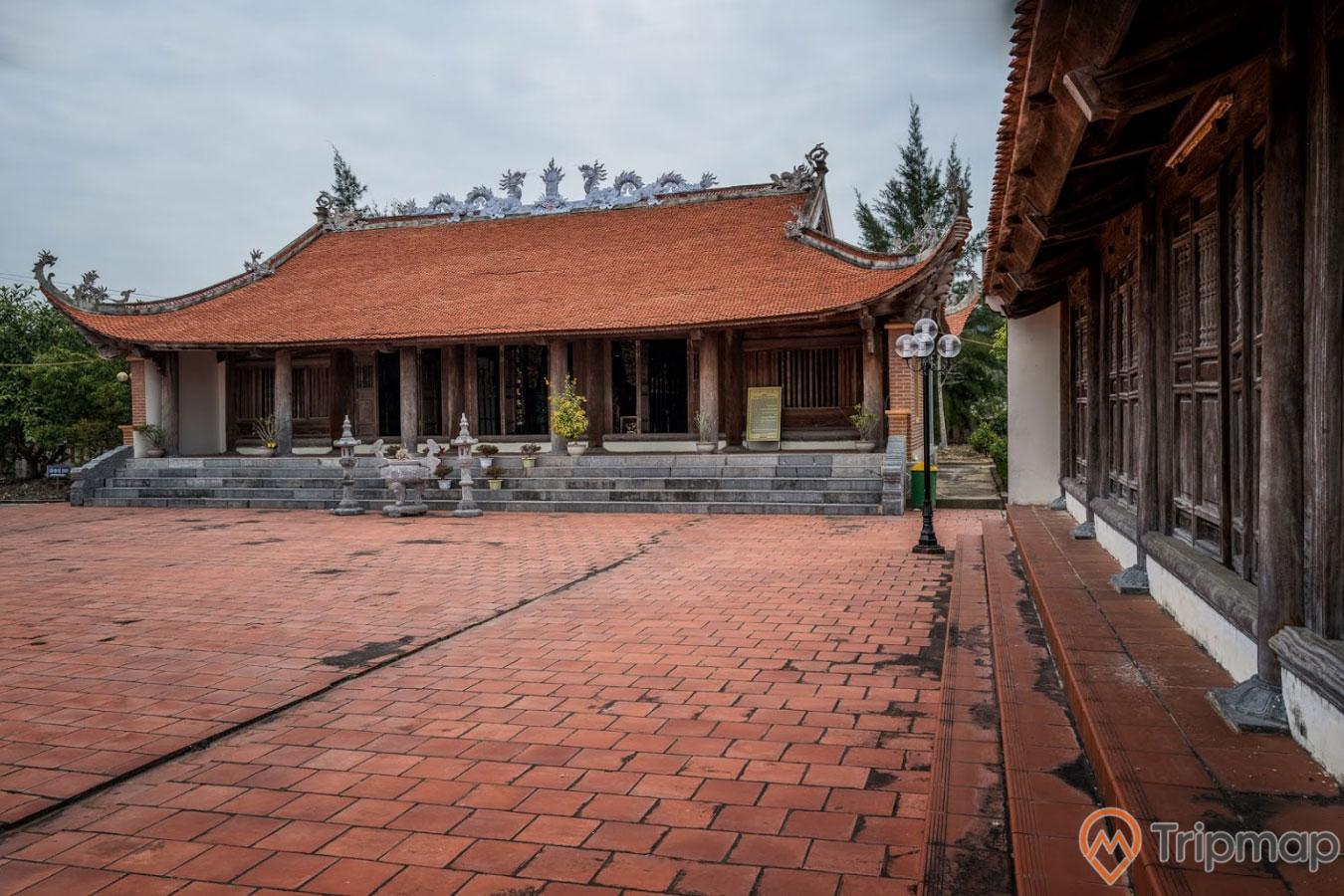Miếu thờ Trần Khánh Dư, nền gạch màu đỏ, mái ngói màu đỏ, trời nhiều mây, ảnh chụp ban ngày