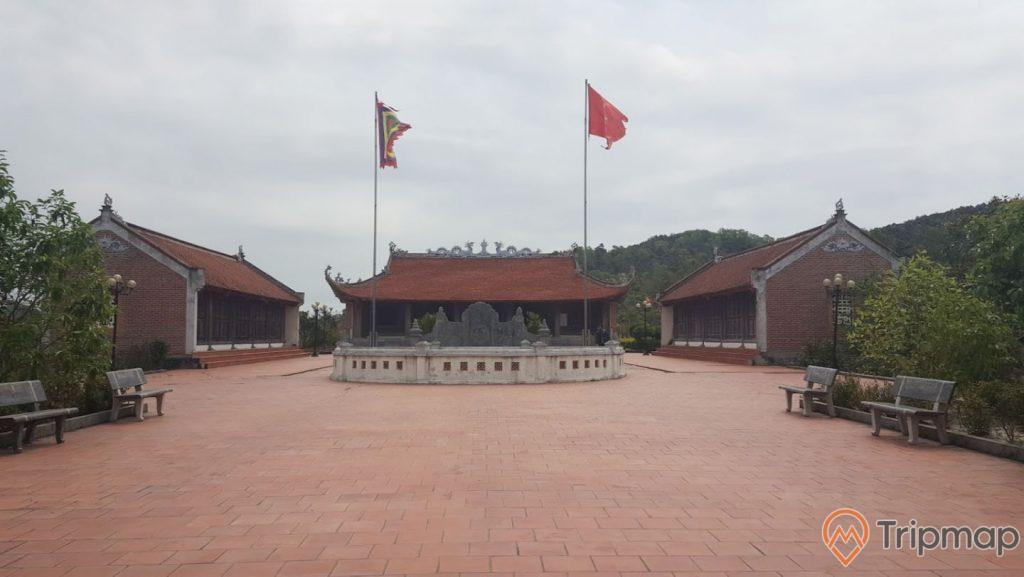 Miếu thờ Trần Khánh Dư, nền gạch màu đỏ, nhiều ghế đá màu xám, trời nhiều mây, lá cờ việt nam, miếu bằng gạch màu đỏ, nhiều cây xanh, ảnh chụp ban ngày