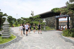 Nhà Bonsai, nền gạch bằng đá màu xám, nhiều người đang đi trên nền gạch màu xám, nhiều cây xanh, trời nắng, ảnh chụp ban ngày