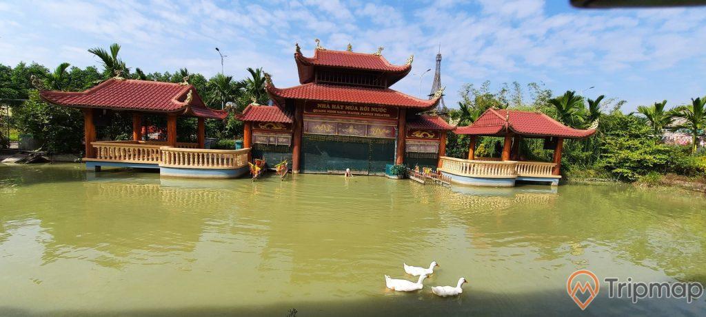 Nhà hát múa rối nước, Quảng Ninh Gate, nhiều mái ngói màu đỏ, bờ hồ có mặt nước màu xanh, đàn vịt màu trắng đang bơi trên mặt nước, trời nắng, nhiều cây xanh phía xa, trời xanh nhiều mây, ảnh chụp ban ngày