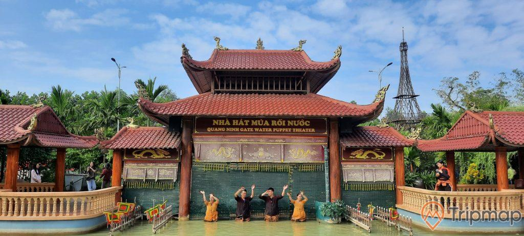 Nhà hát múa rối nước, Quảng Ninh Gate, nhiều mái ngói màu đỏ, nhiều người đang dơ tay đứng dưới nước, trời xanh mây trắng, trời xanh, ngọn tháp ở phía xa, nhiều cây xanh phía xa, ảnh chụp ban ngày