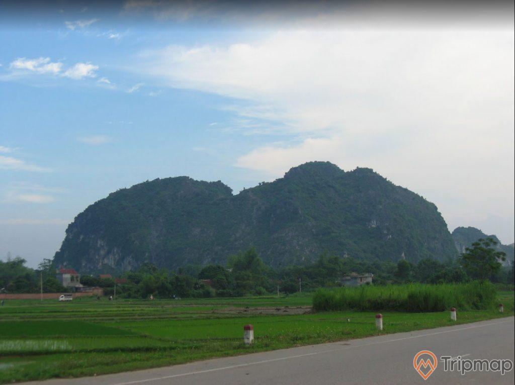 Núi Voi, con đường màu xám, nhiều cột mốc, cánh đồng lúa, nhiều cây xanh, ngọn núi ở phía xa, trời xanh nhiều mây, ảnh chụp ban ngày