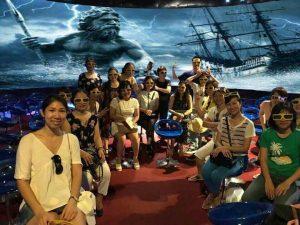 Rạp chiếu phim 12D, nhiều người đang trải nghiệm rạp phim, nền đường bằng tấm vải màu đỏ, bức tranh ngoài biển đằng sau