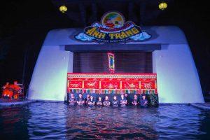 Sân khấu múa rối nước Ánh Trăng, nhiều người mặc áo đen đang đứng dưới nước, một vài người mặc đồ đỏ đang đánh trống, đèn lồng màu vàng, bức tường màu trắng