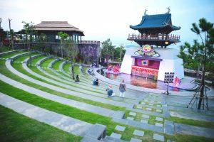 Sân khấu múa rối nước Ánh Trăng, khán đài, thảm cỏ xanh, nhiều người đang ngồi trên dãy ghế bằng đá, mái ngói màu xanh, nhiều cây xanh, ảnh chụp ban ngày