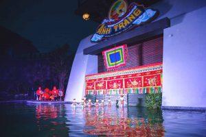 Sân khấu múa rối nước Ánh Trăng, nhiều mô hình người dưới nước, vài người mặc đồ đỏ đang đánh trống, cây xanh dưới nước, nhiều tấm vải màu đỏ có hoa văn