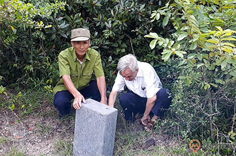 Thành cổ Ngọc Vừng, 2 người lớn tuổi đang ngồi trên nền đất màu nâu, phiến đá màu xám, nhiều cây xanh, ảnh chụp ban ngày