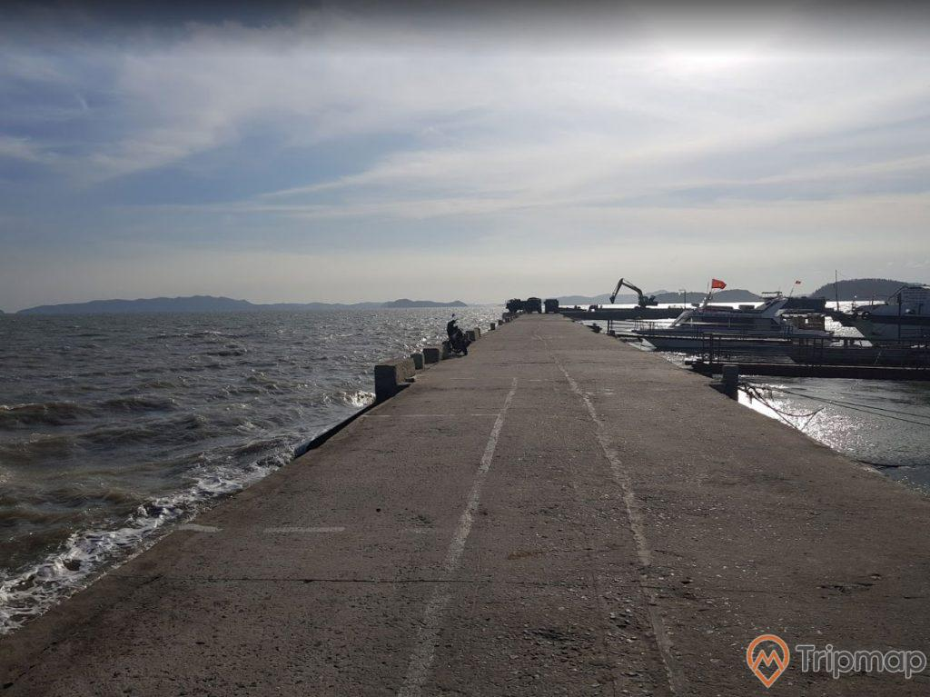 Thương cảng cổ Vân Đồn, bờ đê bằng xi măng màu xám, nước biển xanh, nhiều thuyền đang đỗ ở cảng trời nhiều mây, ảnh chụp ban ngày