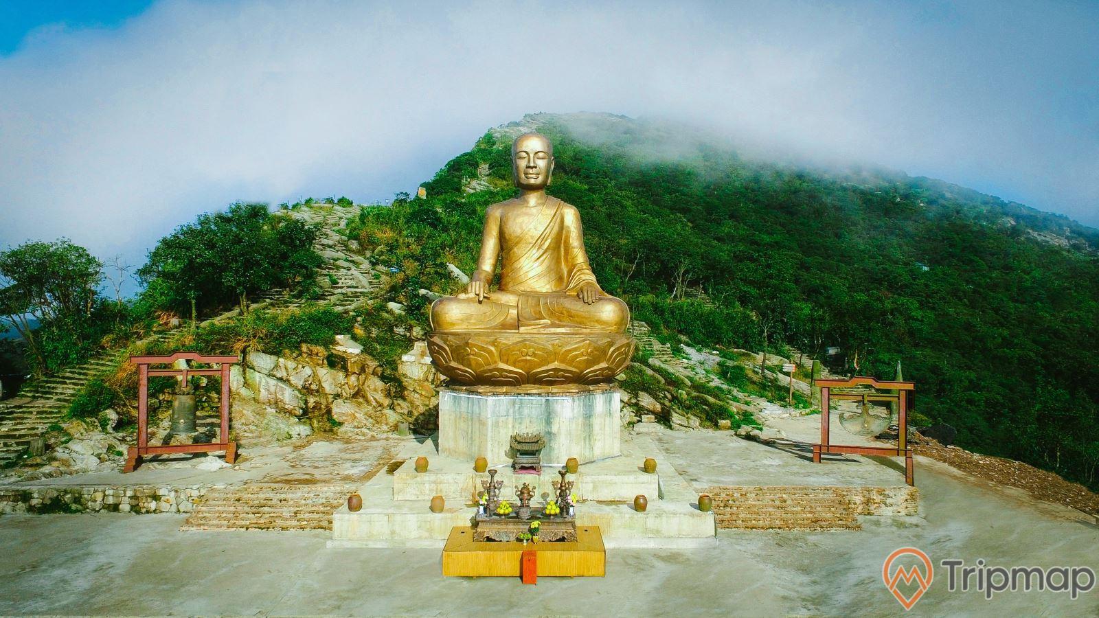 Tượng Phật hoàng Trần Nhân Tông, Yên Tử, tượng bằng đồng, chuông đồng, ngọn núi nhiều cây xanh phía xa, trời nhiều mây, ảnh chụp ban ngày