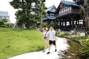 Vườn Nhật Bản Zen Garden, 2 người đang đi bộ trên nền đường màu xám, nhiều cây xanh, nhà có mái ngoái màu xanh, hồ nước nhiều viên sỏi, ảnh chụp ban ngày