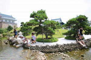 Vườn Nhật Bản Zen Garden, nhiều cây xanh, nhiều người đang ngồi cạnh hồ nước, nhiều viên sỏi, ảnh chụp ban ngày