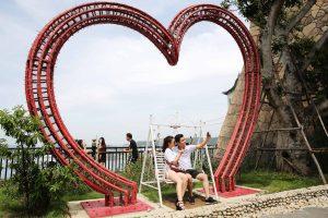Vườn Nhật Bản Zen Garden, 2 người đang ngồi ghế màu trắng chụp ảnh, trái tim đỏ khổng lồ, thảm cỏ xanh phía sau, trời nhiều mây, ảnh chụp ban ngày