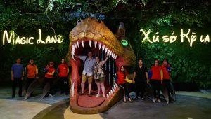 Xứ sở kỳ lạ, Magic land, mô hình đầu khủng long đang nhe răng, nhiều người đang chụp ảnh, mô hình vườn cây phía sau
