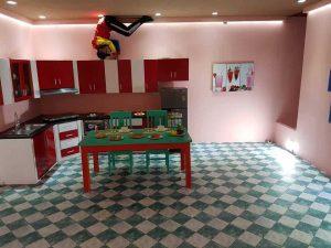 Xứ sở lộn ngược, Magic land, nền nhà bằng gạch màu xanh trắng, bàn ăn màu xanh, gian bếp màu đỏ trắng, tường nhà màu hồng, người đang nằm trên trần nhà