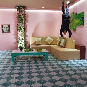 Xứ sở lộn ngược, Magic land, nền nhà bằng gạch màu xanh trắng, bộ bàn ghế sofa màu vàng, bàn uống nước màu trắng, bức tường màu hồng, người đàn ông đang chống tay vào ghế sofa