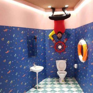 Xứ sở lộn ngược , Magic land, nhà vệ sinh lộn ngược, bệ xí, bồn rửa tay, phao cứu hộ, bức tường màu xanh nhiều họa tiết