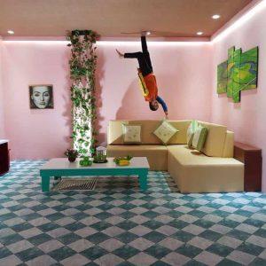 Xứ sở lộn ngược, Magic land, nền nhà bằng gạch màu xanh trắng, bộ bàn ghế sofa màu vàng, bàn uống nước màu trắng, bức tường màu hồng, người phụ nữ đang chống tay vào ghế sofa