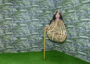 Xứ sở lộn ngược – Magic land, thảm cỏ màu xanh, người phụ nữ đang trải nghiệm trò chơi, bức tường hình viên gạch