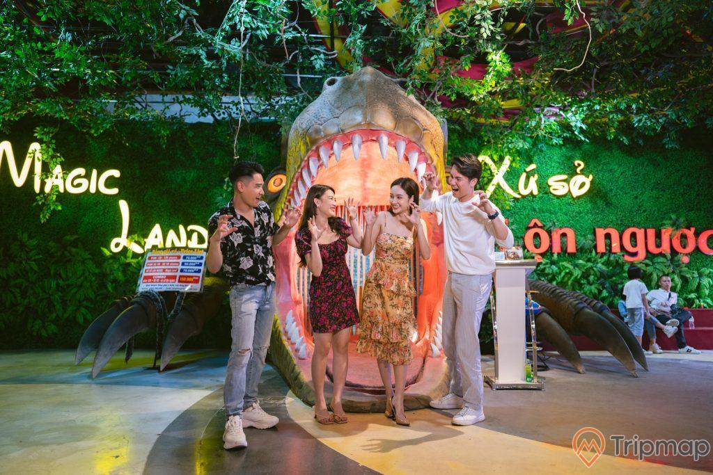Xứ sở lộn ngược, Magic land, mô hình đầu khủng long đang nhe răng, nhiều người đang đứng trên nền gạch có hoa văn, 4 người đang dơ tay chụp ảnh, mô hình cây xanh ở phía sau