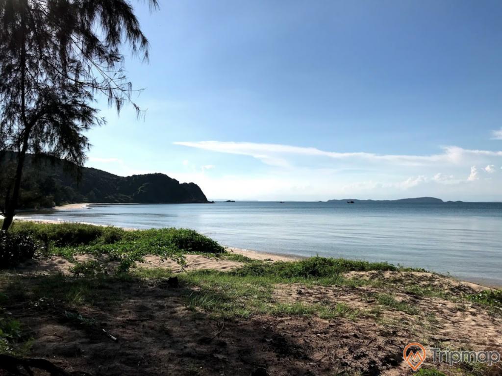 Bãi tắm Hải Quân, mặt nước biển màu xanh, ngọn núi nhiều cây xanh phía xa, trời nắng, trời xanh nhiều mây, ảnh chụp ban ngày