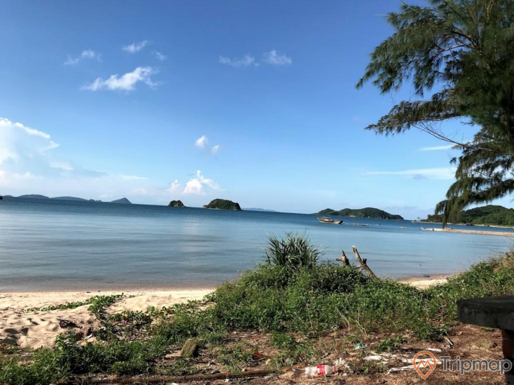 Bãi biển Hải Quân, mặt nước biển màu xanh, nhiều ngọn núi ở phía xa, trời xanh mây trắng, trời nắng, ảnh chụp ban ngày