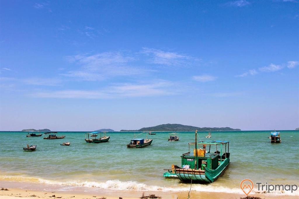 Những chiếc thuyền tại bãi biển Hồng Vàn, ảnh chụp ngoài trời, bầu trời trong xanh ít mây, đảo phía xa, nhiều chiếc thuyền đang neo đậu tại bãi biển,