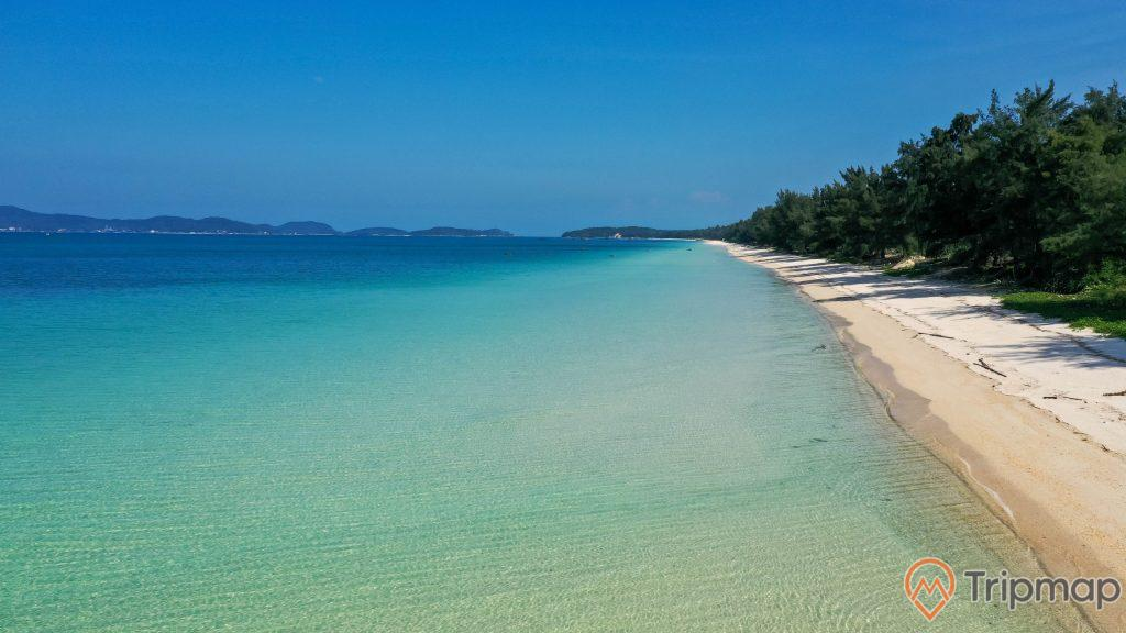Quang cảnh tại bãi biển Hồng Vàn, ảnh chụp ngoài trời, bầu trời trong xanh, cây cối xanh tươi tại bãi biển, đảo phía xa,