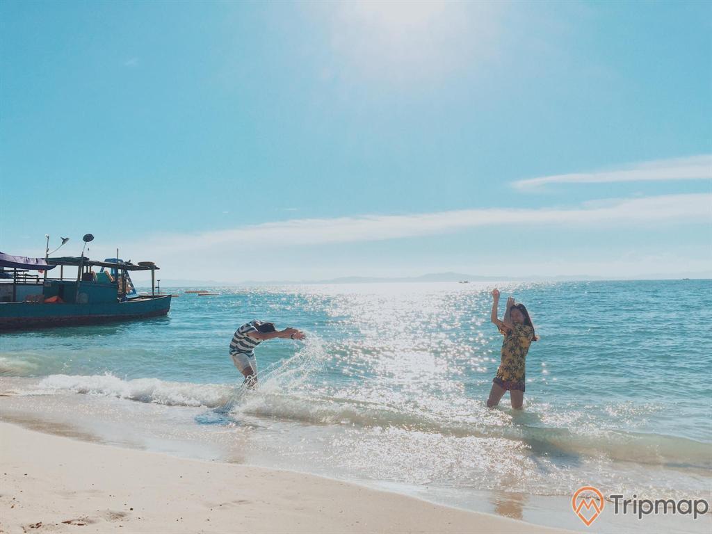 Hai du khách nô đùa trên bãi biển Hồng Vàn, ảnh chụp ngoài trời, bầu trời trong xanh ít mây và có nắng, chiếc thuyền đậu ở bãi biển,