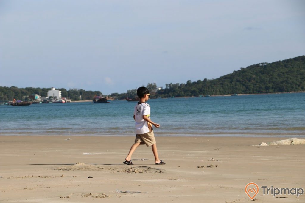 Cậu bé đang đi trên bãi biển Tình Yêu, bầu trời nhiều mây, ảnh chụp ngoài trời, đảo phía xa xa, thuyền trên biển phía xa