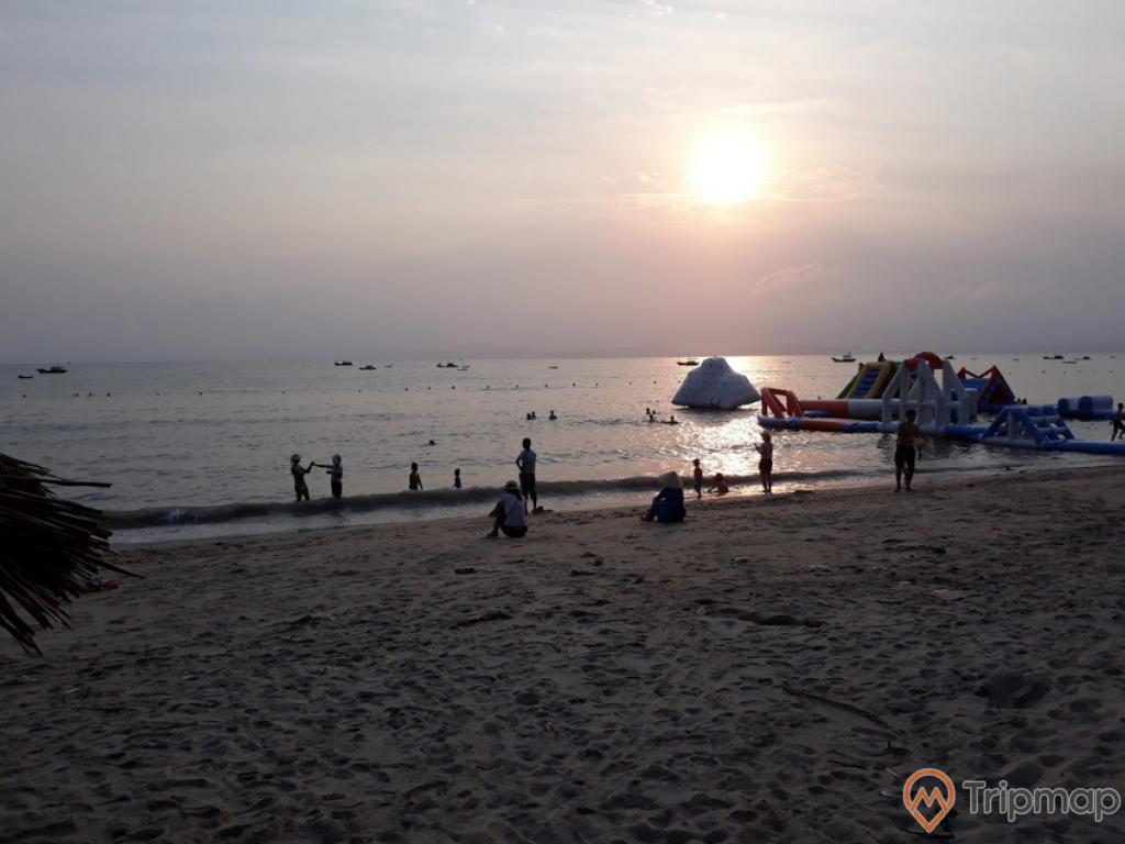 Hoạt động vui chơi tại bãi biển Tình Yêu, bầu trời nhiều mây có mặt trời, mọi người đang tắm và vui chơi gần bờ biển, nhà phao vui chơi trên bãi biển