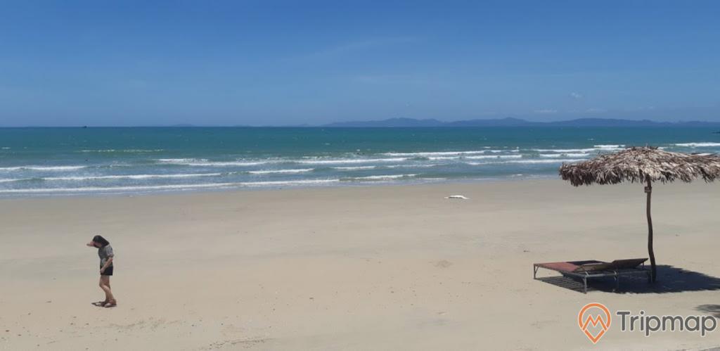 Quang cảnh buổi trưa nắng tại bãi biển Tình Yêu, bầu trời trong xanh, chiếc ô lá cọ và chiếc giường xếp trên bài biển, bãi cát và biển cô tô