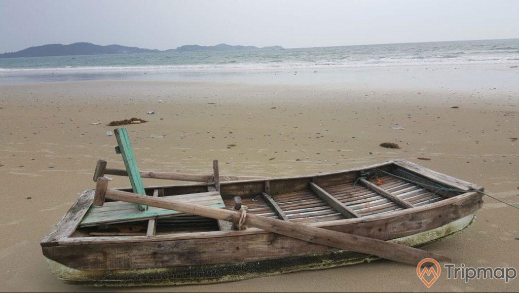 Chiếc thuyền gỗ trên bờ cát bãi biển Tình Yêu, ảnh chụp ngoài trời, bầu trời nhiều mây, đảo phía xa,