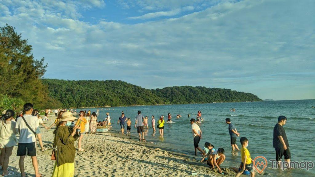 Du khách vui chơi tại bãi biển Vàn Chảy, ảnh chụp ngoài trời, bầu trời nhiều mây, cây cối trên đảo xanh tươi gần bãi biển