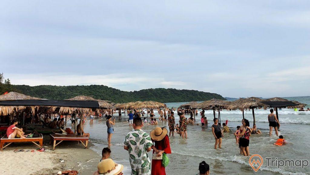 Khu vui chơi cho du khách tại bãi biển Vàn Chảy, ảnh chụp ngoài trời, bầu trời nhiều mây, mọi người đang đứng trên bãi biển, những chiếc ô bằng lá cọ che nắng ở bãi biển