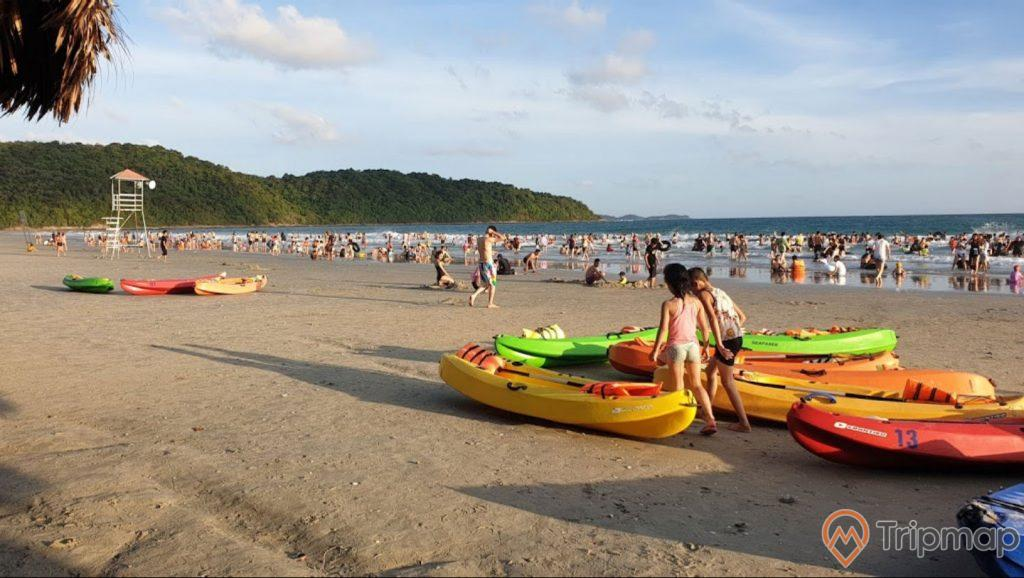 bãi biển Vàn Chảy, bầu trời nhiều mây, cây cối xanh tươi trên đảo gần bãi tắm, 2 đứa trẻ đứng cạnh những chiếc thuyền phao, mọi người đang tắm ở bãi biển vàn chảy