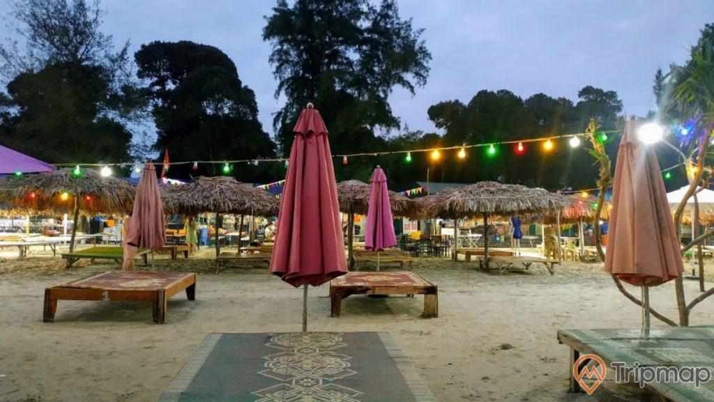 Khu nghỉ dưỡng ngay tại bãi biển Vàn Chảy, ảnh chụp vào lúc buổi chiều tối, cây cối xanh tươi gần bãi biển, những chiếc ô lá cọ và chiếc, ánh đèn sáng vào buổi tối,