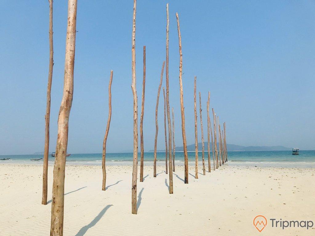 Hàng chông gỗ cắm thẳng trên bãi biển Vàn Chảy, bầu trầu trong xanh, ảnh chụp ngoài trời, 1 chiếc thuyền đang neo đậu gần bãi biển
