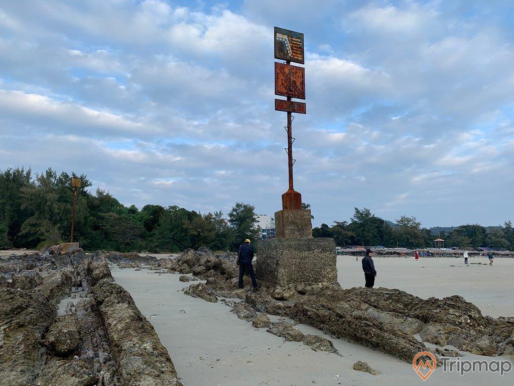 bãi biển vàn chảy, ảnh chụp ngoài trời, bầu trời nhiều mây hai người mặc áo đen đang đứng trên bãi đá, cây cối xanh tươi trên đảo gần bãi biển