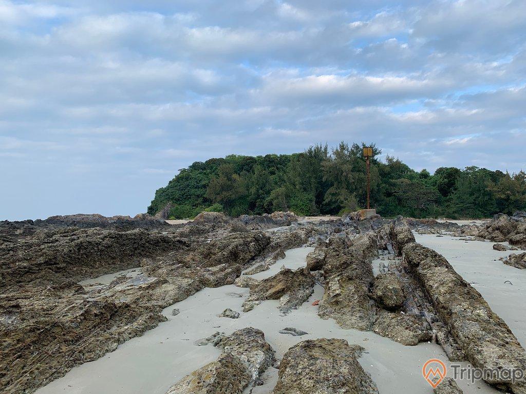 ảnh chụp ngoài trời, bầu trời nhiều mây, cây cối xanh tươi, bãi đá trên bãi biển vàn chảy