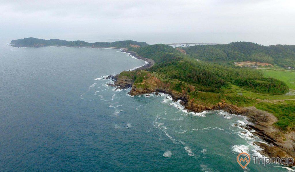 Toàn cảnh địa điểm tham quan bãi đá cầu mỵ (bãi đá móng rồng), ảnh chụp từ trên cao, cây cối xanh tươi gần bãi đá, bầu trời nhiều mây